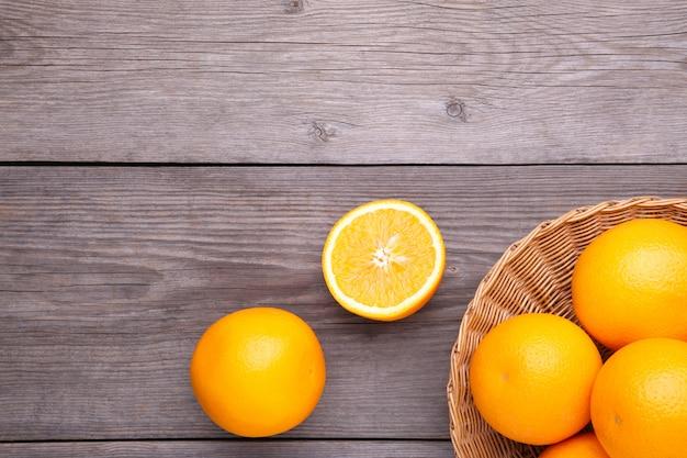 Oranje fruit in mand op een grijze achtergrond