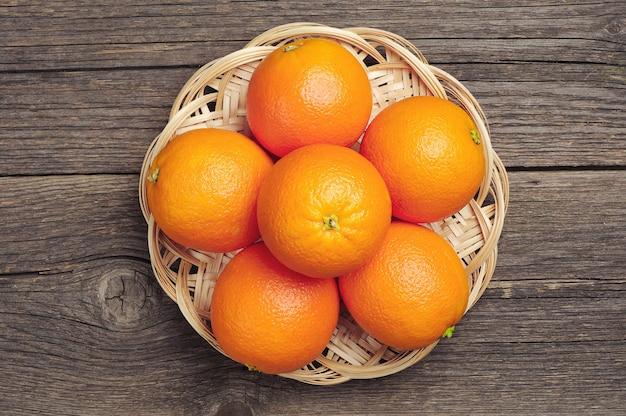 Oranje fruit in rieten plaat op vintage houten tafel. bovenaanzicht