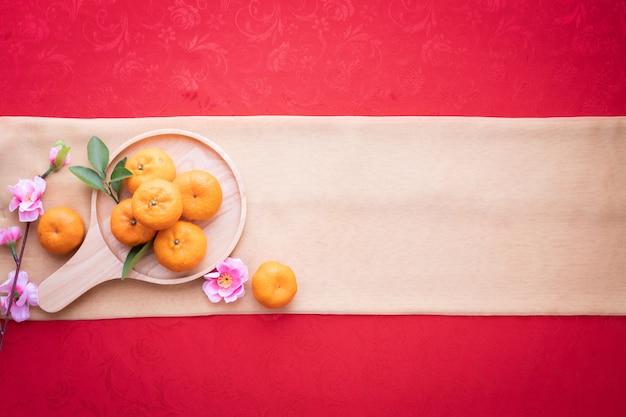 Oranje fruit, roze kersenbloesem met kopie ruimte voor tekst op rode textuur achtergrond.
