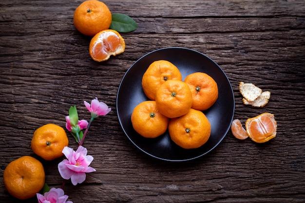 Oranje fruit, roze kersenbloesem op houten tafel, viering chinees nieuwjaar festival achtergrond.