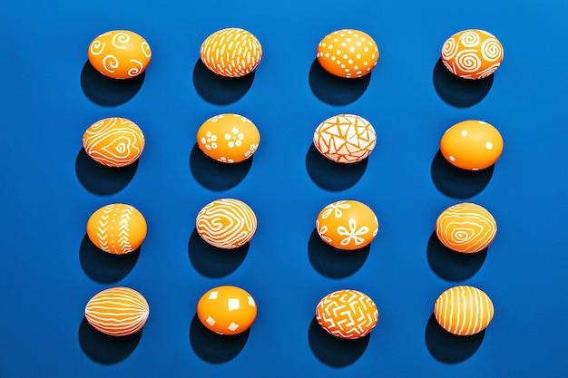 Oranje gekleurd paaseierenpatroon op contrasterend blauw oppervlak