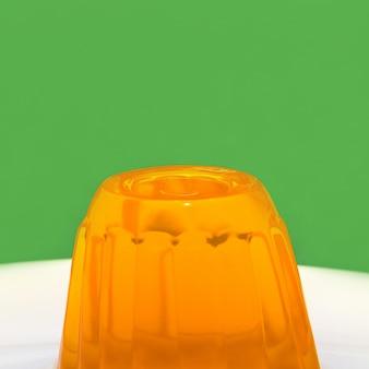 Oranje gelatine op een witte plaat en groene muur