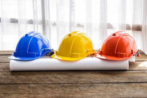 Oranje, gele, blauwe harde veiligheidshelm bouwhoed voor veiligheidsproject van arbeider als ingenieur of arbeider