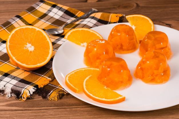 Oranje gelei en oranje plakjes op een witte plaat
