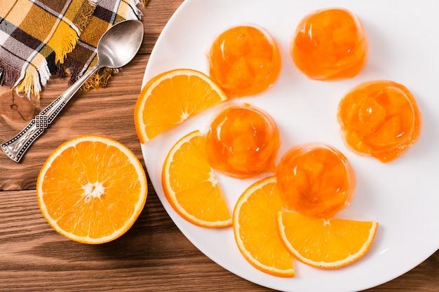 Oranje gelei en plakjes sinaasappel op een plaat op een houten tafel