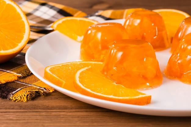 Oranje gelei en sinaasappelen op een plaat op een houten tafel