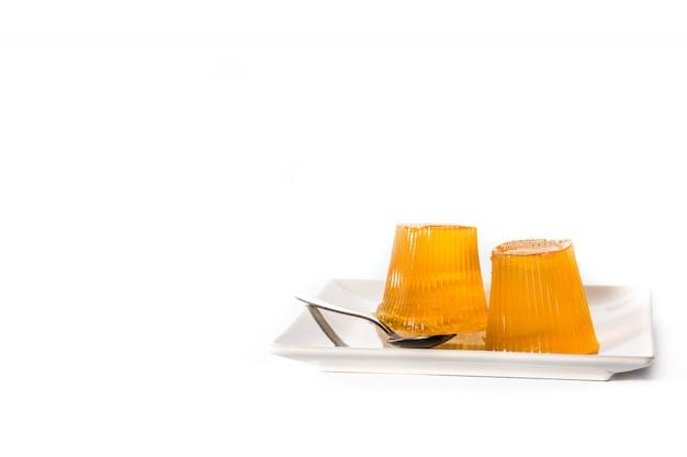 Oranje gelei op een plaat die op witte achtergrond wordt geïsoleerd. kopieer ruimte