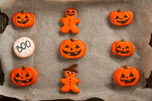 Oranje gemberkoekjes voor halloween liggen op een bakpapier. koekje in pompoenvorm. bovenaanzicht. heerlijke koekjes.