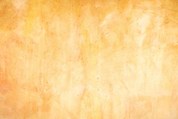 Oranje gepleisterde muren met schade. lege lamb met oneffen oppervlak. a time shattered plaster. lagen van bouwmaterialen, gips, cement, whitewash en bakstenen.
