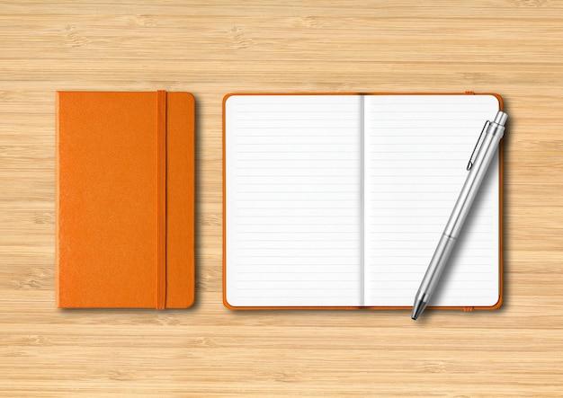 Oranje gesloten en open bekleed notebooks met een pen mockup geïsoleerd op houten