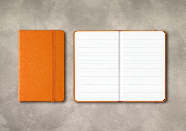Oranje gesloten en open bekleed notitieboekjemodel dat op concrete achtergrond wordt geïsoleerd
