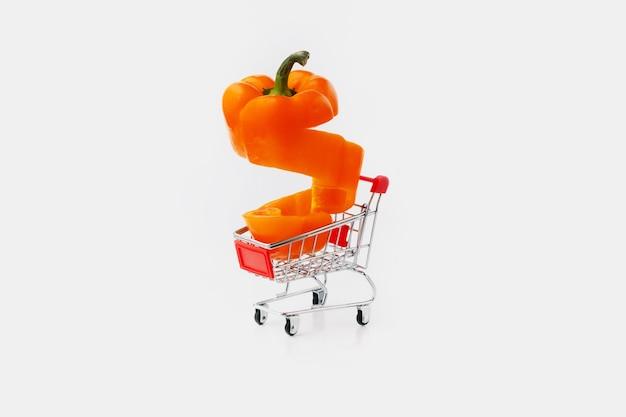 Oranje gesneden paprika peper in een winkelwagentje op grijs