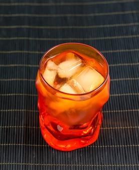 Oranje glas water met ijs op zwarte bamboe oppervlak