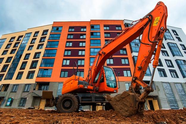 Oranje graafmachine graaft grond tegen de achtergrond van een nieuw huis