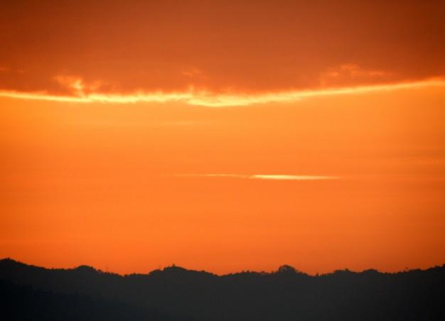 Oranje gradatie van zonsondergang bewolkte hemel over het silhouet van bergketen, thailand