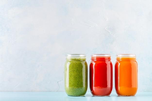 Oranje / groen / rood gekleurde smoothies / sap in een potje