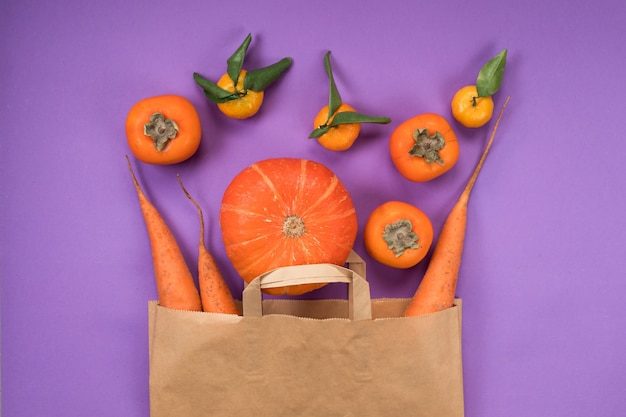 Oranje groenten en fruit in ambachtelijke papieren zak op de violette achtergrond.