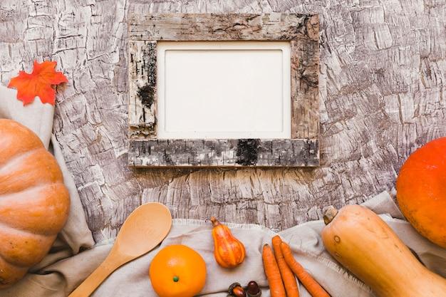 Oranje groenten en fruit in de buurt van lepel en frame