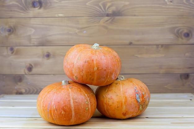 Oranje halloween-pompoenen op witte planken, vakantiedecoratie.