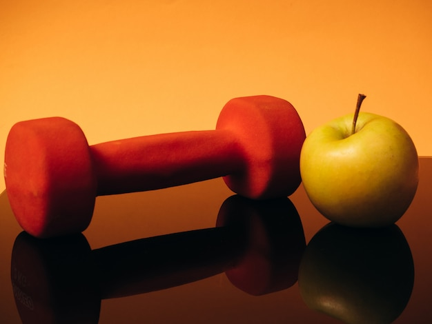 Oranje halters voor fitness en appel op een oranje achtergrond. gereflecteerd door het glazen oppervlak van de balans. concept van sport en een gezonde levensstijl.