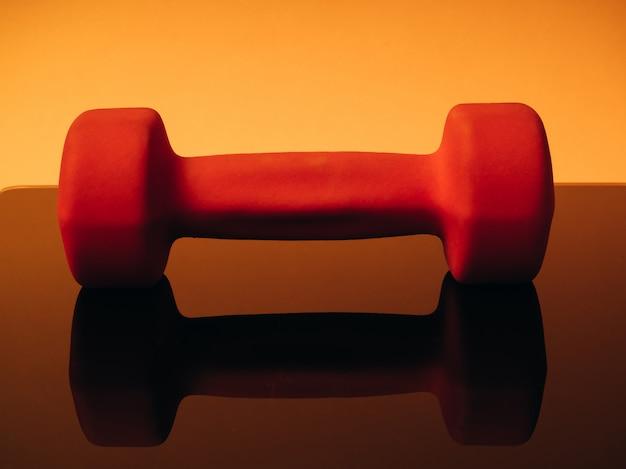 Oranje halters voor fitness op een oranje achtergrond. gereflecteerd door het glazen oppervlak van de balans. concept van sport en een gezonde levensstijl.