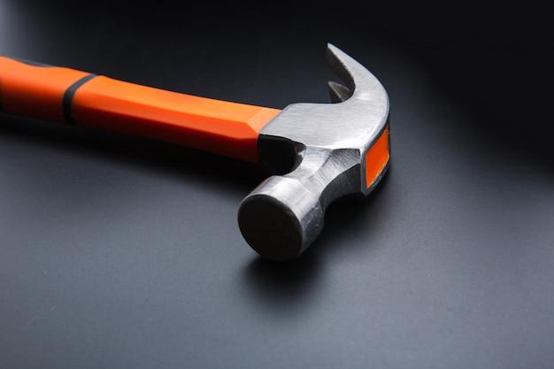 Oranje hamer op donkere matte achtergrond, close-up