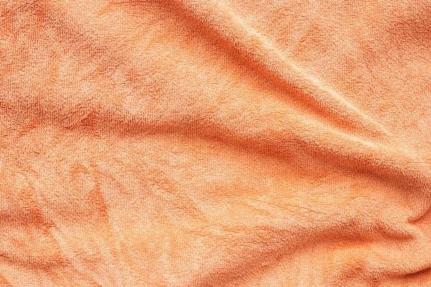 Oranje handdoek stof textuur oppervlak close-up achtergrond