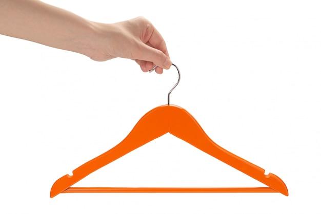Oranje hanger in geïsoleerde vrouwenhand.