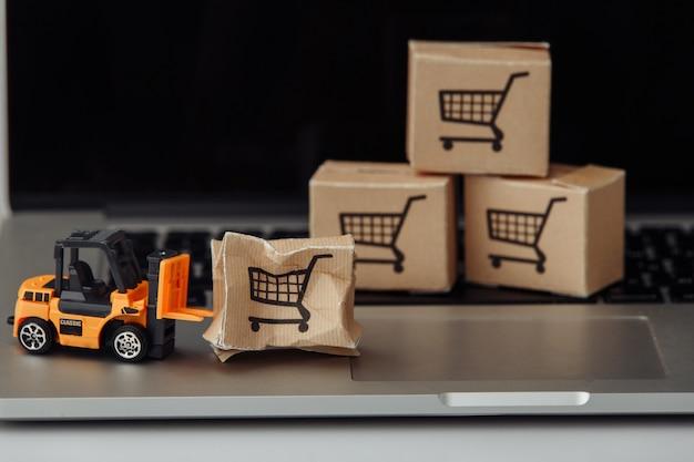 Oranje heftruckmodel en gebroken kartonnen doos op een toetsenbord