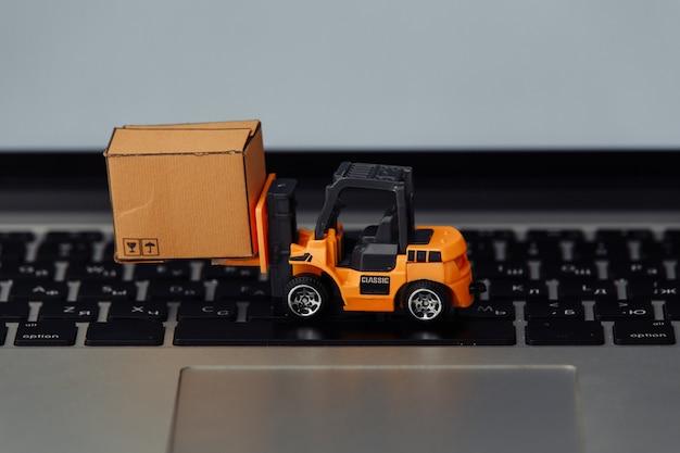 Oranje heftruckmodel en kartonnen doos op een toetsenbord. koerier dienstverleningsconcept.