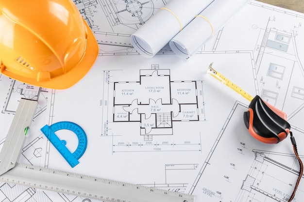 Oranje helm, potlood, architecturale constructietekeningen, meetlint