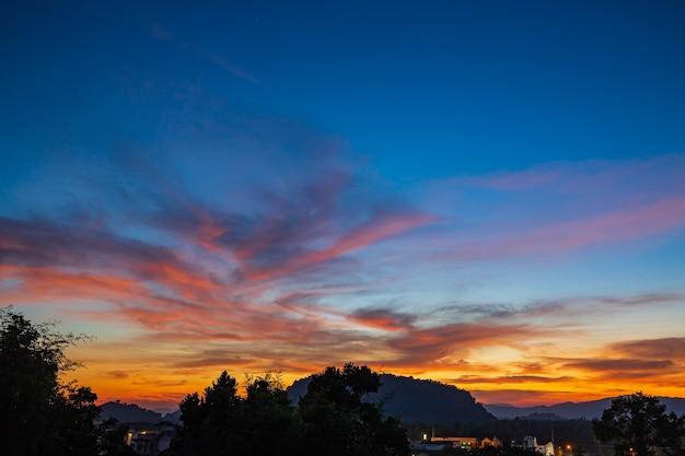 Oranje hemellicht warm van de zon voegt een prachtige gloed toe aan de wolken