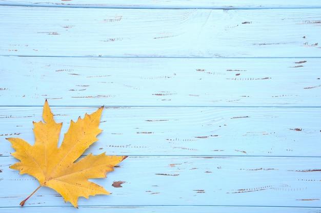 Oranje herfstbladeren op een blauwe tafel