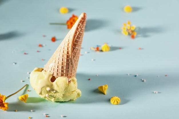 Oranje ijs met wafel kegel op blauwe achtergrond met gele bloemen.