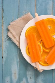 Oranje ijslollys op blauwe houten tafelblad bekijken