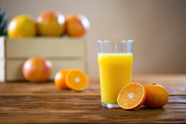 Oranje in tweeën gesneden liggend op een houten tafel naast een glas vers geperst sap