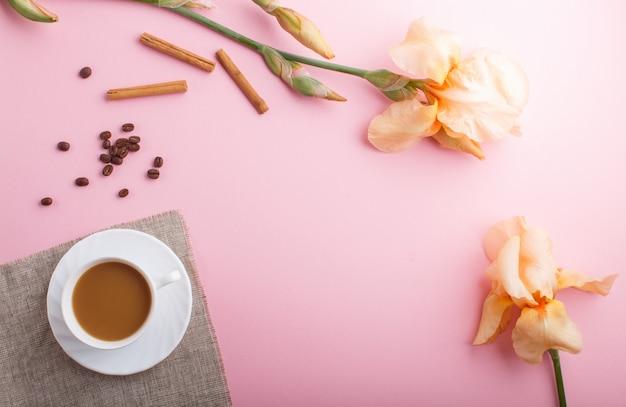 Oranje iris bloemen en een kopje koffie op pastel roze achtergrond.