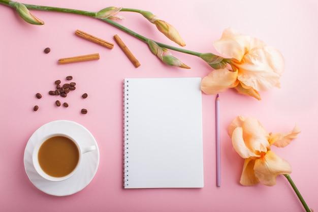 Oranje irisbloemen en een kop van koffie met notitieboekje op pastelkleurroze