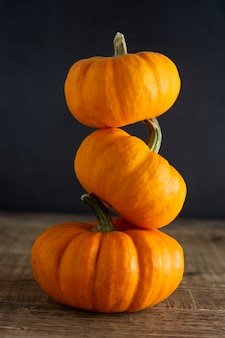 Oranje kleine pompoenen op donker hout