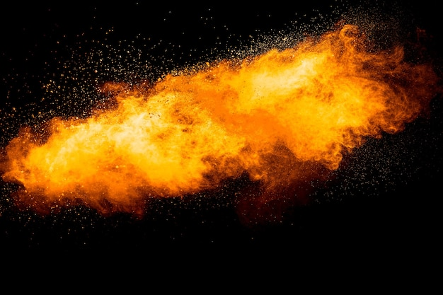 Oranje kleur poeder explosie op zwarte achtergrond.