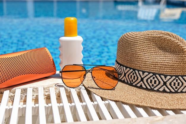 Oranje kleurige strandaccessoires bij zwembad. zonnebrandcrème, zonnebril, muziekspeaker en strohoed.