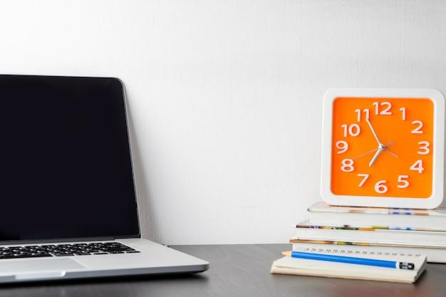 Oranje klok op kantoor tafel met laptop