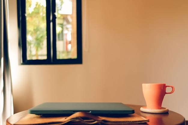 Oranje koffiekopje en laptop op de tafel in het café.