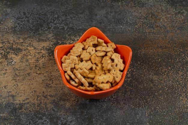 Oranje kom crackers op marmer.