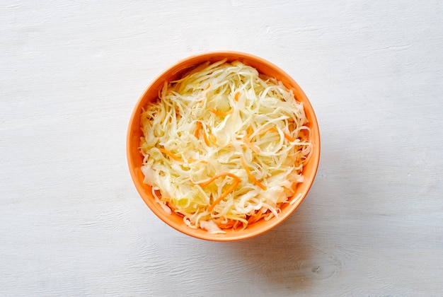 Oranje kom geraspte groenten met hierboven kool van