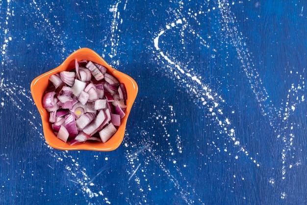 Oranje kom met gesneden paarse uien op marmeren oppervlak