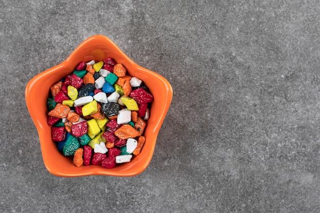 Oranje kom met kleurrijke stenen snoepjes op stenen tafel.