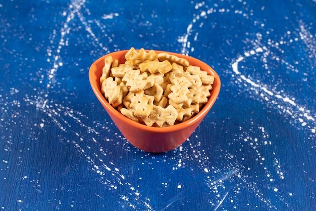 Oranje kom zoute kleine crackers op marmeren oppervlak.