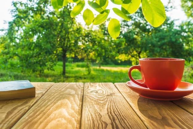 Oranje kop warme koffie en een boek op een houten tafel in een groene tuin in de ochtend
