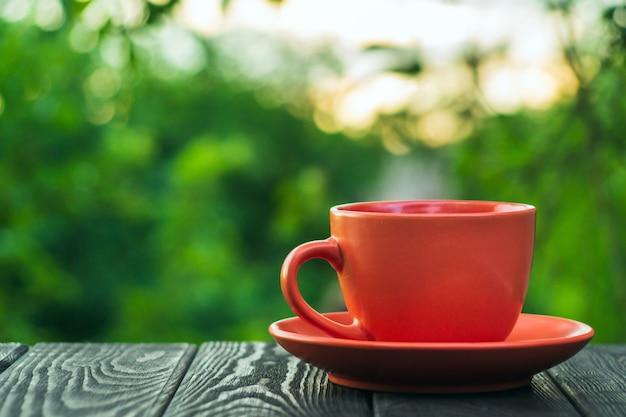 Oranje kop warme koffie op een houten tafel in een groene tuin in de ochtend of avond